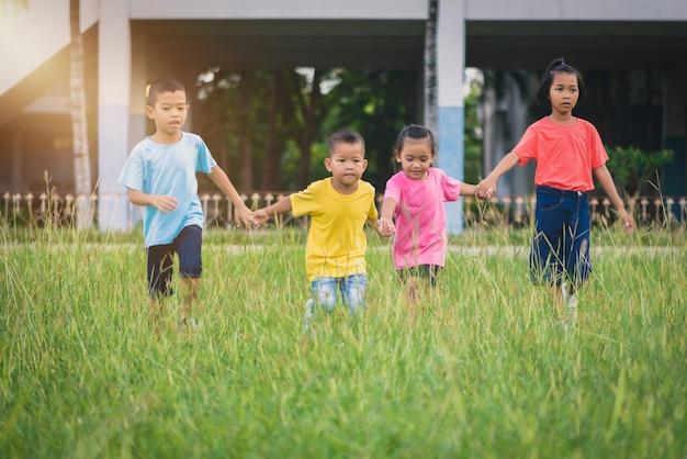 Grupa azjatykci dzieci trzyma ręki, biega lub chodzi wpólnie na trawy polu przy szkołą