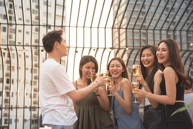 Grupa azjatykci wieloskładnikowy płeć trzyma szkło wino gadka wraz z przyjaciółmi podczas gdy świętujący przyjęcia tanecznego na plenerowym dachu klubie nocnym, czasu wolnego styl życia młody przyjaźni przyjemności pojęcie.