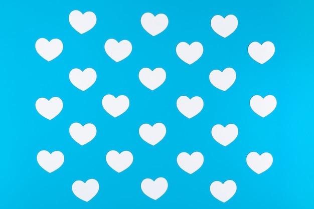 Grupa białych serc na niebieskim tle