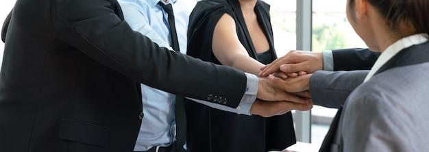 Grupa biznes drużyna stawia ręki wpólnie. koncepcja współpracy i pracy zespołowej