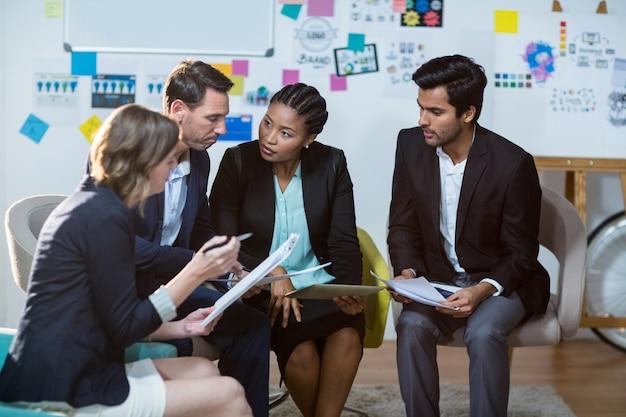 Grupa biznesmeni dyskutuje przed whiteboard