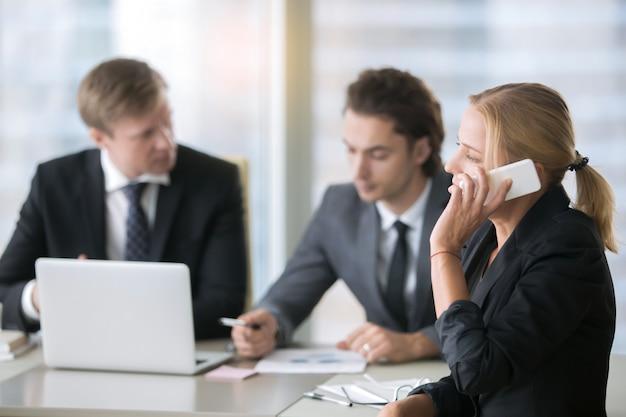 Grupa biznesmeni przy biurowym biurkiem z laptopem