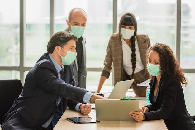 Grupa biznesmeni spotykający się w biurze noszą maskę medyczną chroniącą covid19 lub koronawirusa