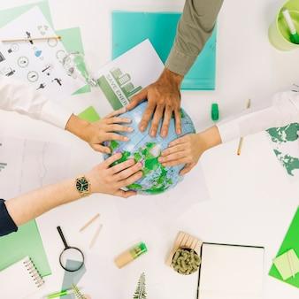 Grupa biznesmeni umieszcza ich ręki na kuli ziemskiej