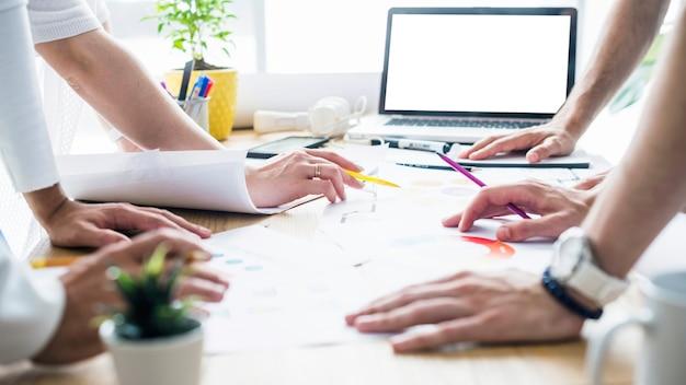 Grupa biznesmeni wręcza nad biurkiem przy miejscem pracy
