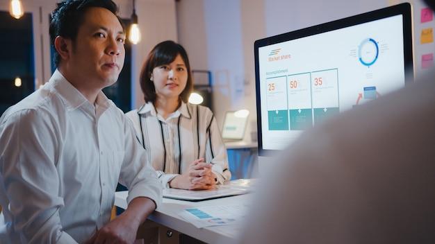 Grupa biznesmenów i bizneswoman z azji korzystających z prezentacji komputerowych i pomysłów na spotkanie z komunikacją podczas burzy mózgów