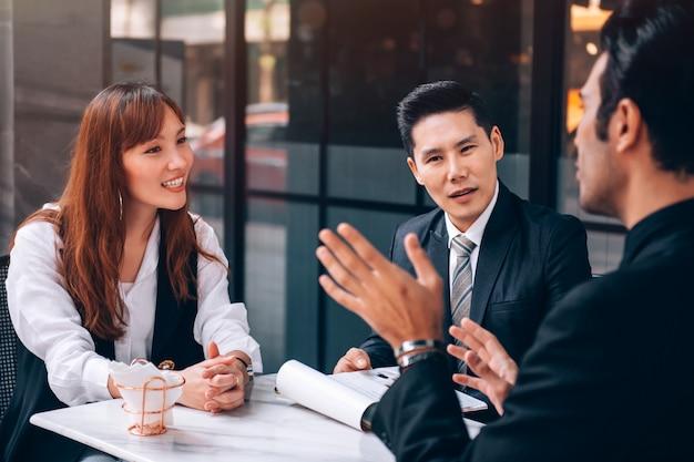 Grupa biznesmenów i bizneswomanów rozmawiających o nowym projekcie biznesowym i planie marketingowym z partnerem w coffee shop w business distric location