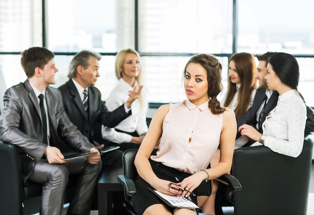Grupa biznesmenów omawiających w biurze politykę firmy.