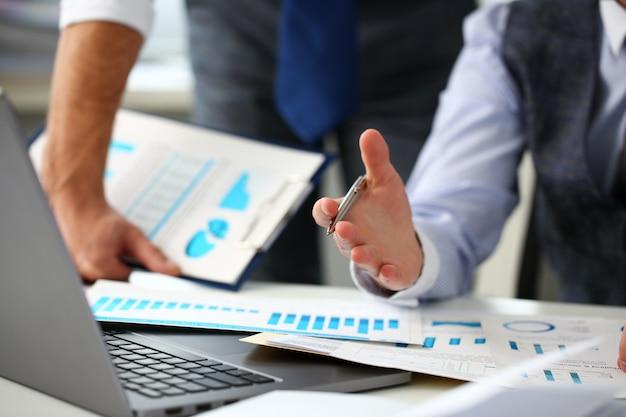Grupa biznesmenów punkt ramienia srebrnym piórem na komputerze przenośnym