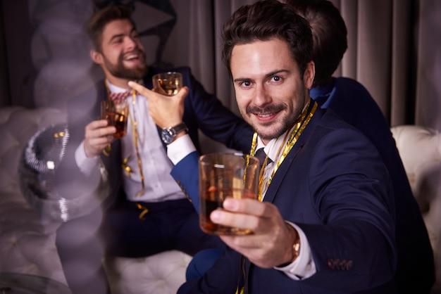 Grupa biznesmenów z whisky cieszących się w klubie nocnym