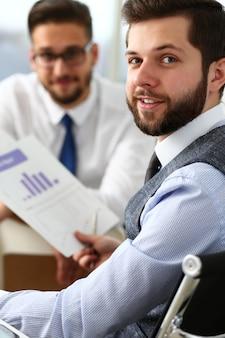 Grupa biznesmenów z wykresem finansowym i srebrnym piórem