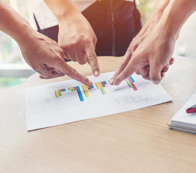 Grupa biznesowa zgadza się i jako zespół wskazuje rękę na papierze milimetrowym