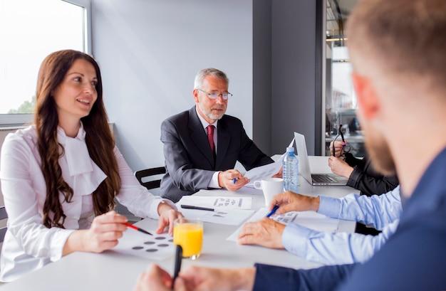 Grupa biznesowi ludzie ruchliwie dyskutować pieniężną sprawę podczas spotkania