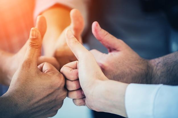 Grupa biznesu pracy zespołowej strony togetrher z kciuki do góry
