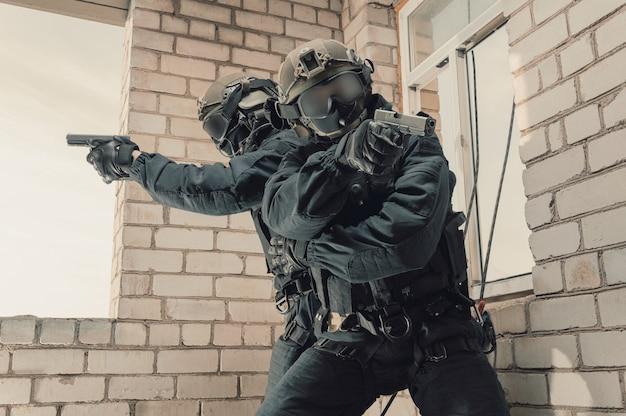 Grupa bojowników sił specjalnych szturmuje budynek przez okno