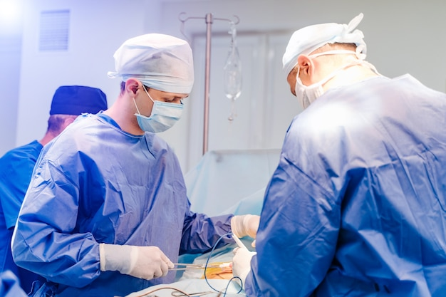 Grupa chirurgów w sali operacyjnej ze sprzętem chirurgicznym