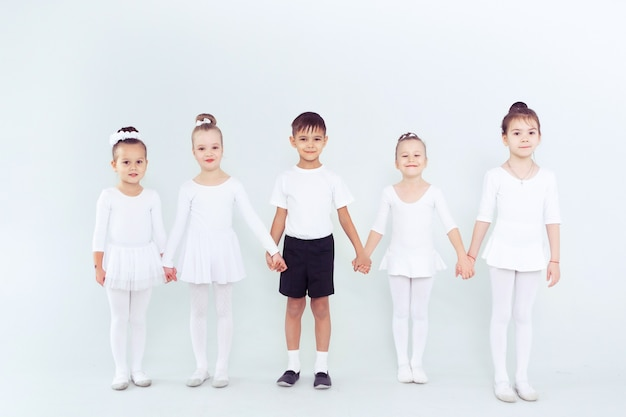 Grupa chłopców i dziewcząt tańczących w białej klasie lub studio, uśmiechając się i przytulając się razem