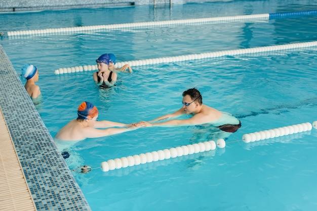 Grupa chłopców i dziewcząt trenuje i uczy się pływać w basenie z instruktorem. rozwój sportu dziecięcego.
