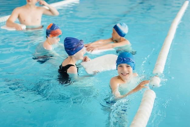 Grupa chłopców i dziewcząt trenuje i uczy się pływać w basenie z instruktorem