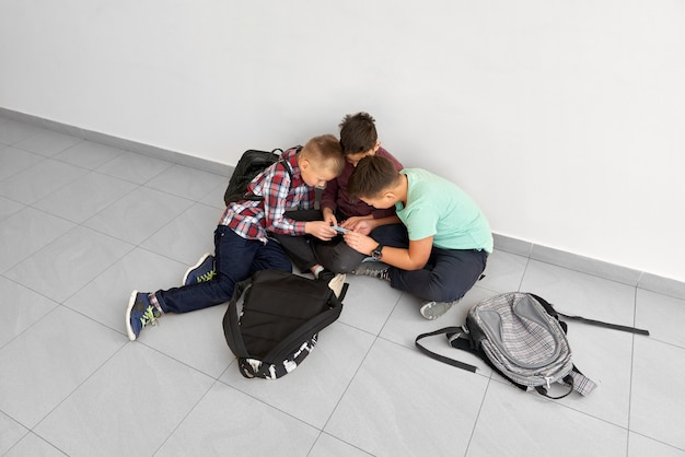 Grupa chłopców siedzi na szkolnym korytarzu na podłodze, patrząc, dyskutując razem lub pokazując coś.