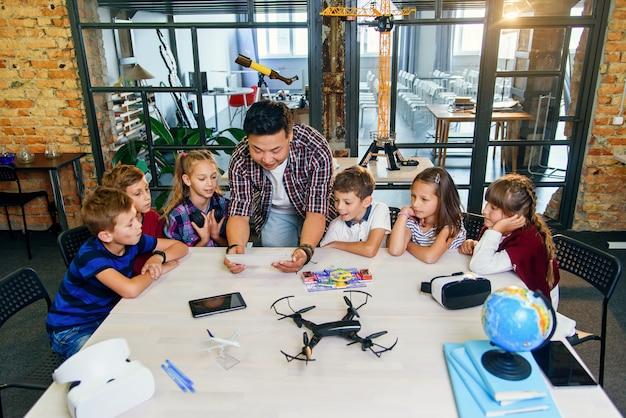 Grupa ciekawskich dzieci w wieku szkolnym słucha koreańskiego nauczyciela, który używa tabletu do wyświetlania edukacyjnych filmów dla uczniów.