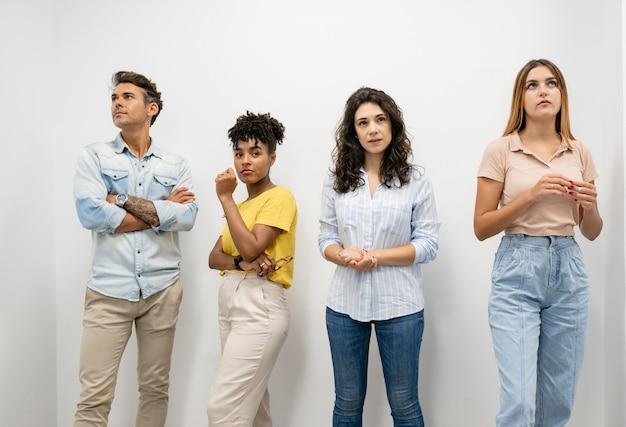 Grupa cowokringowych mężczyzn i kobiet stojących na ścianie