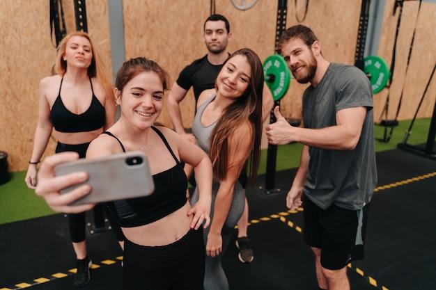 Grupa crossfit robi sobie selfie z trenerem po skończonym treningu na siłowni.