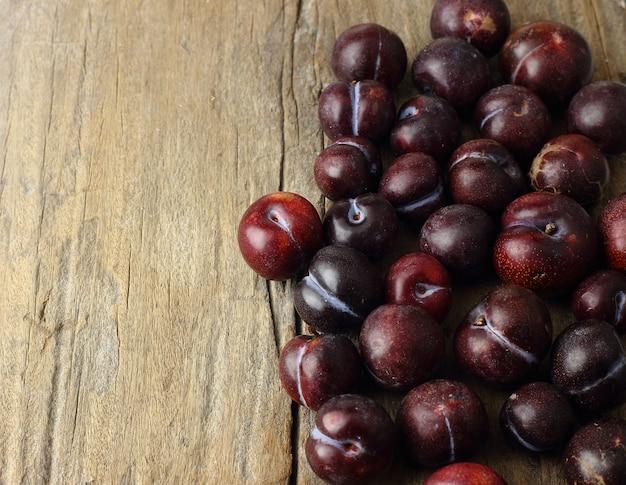 Grupa czerwone śliwkowe owoc na drewnianym stole