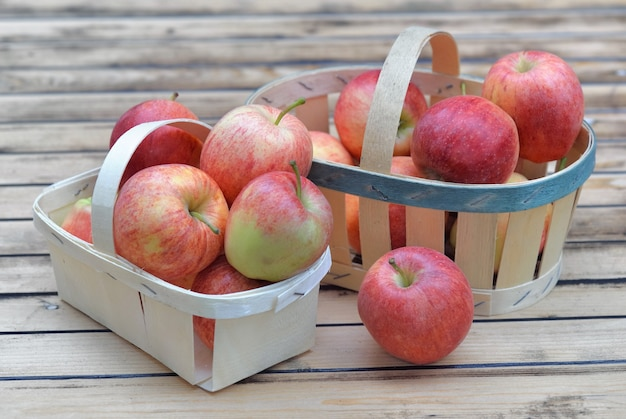 Grupa czerwonych jabłek w koszyczkach na drewnianym stole