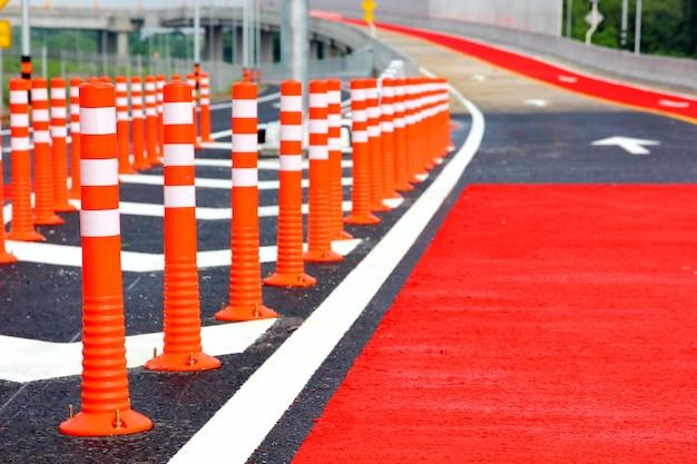 Grupa czerwonych stożków drogowych zainstalowanych na nowym drogowym znaku ostrzegawczym dla bezpieczeństwa jazdy