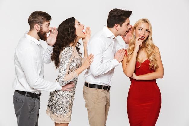 Grupa czterech inteligentnie ubranych wesołych ludzi, którzy opowiadają sobie tajemnice na białym tle nad białym
