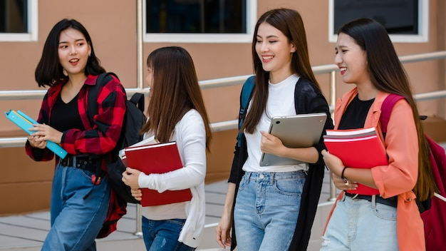 Grupa czterech młodych atrakcyjnych azjatyckich dziewcząt studentów idących razem po schodach w kampusie uniwersyteckim, rozmawiających i śmiejących się z radości. koncepcja edukacji i życia studentów.