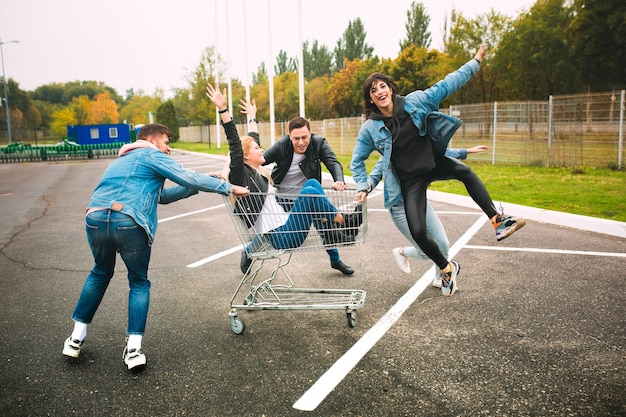 Grupa czterech młodych, zróżnicowanych przyjaciół w dżinsowych strojach wygląda beztrosko