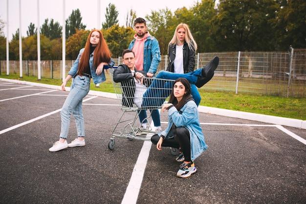 Grupa czterech młodych, zróżnicowanych przyjaciół w dżinsowych strojach wygląda na beztroską młodą i szczęśliwą