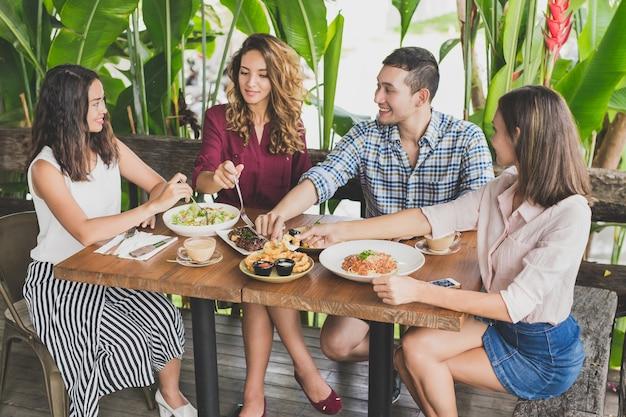 Grupa czterech najlepszych przyjaciół jedzących razem lunch w kawiarni
