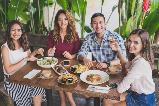 Grupa czterech najlepszych przyjaciół jedzących razem obiad w kawiarni, patrząc na kamery