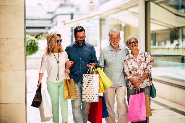 Grupa czterech osób i rodzina chodzą razem na zakupy, trzymając dużo toreb z zakupami po zakupie - czarny piątek lub cyber poniedziałek i czas wyprzedaży