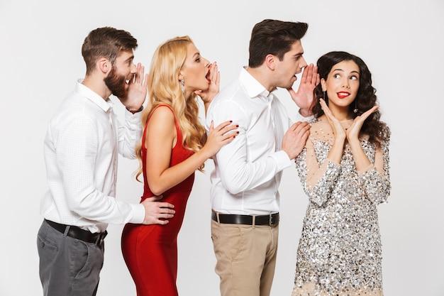 Grupa czterech pięknych ludzi elegancko ubranych, opowiadających sobie tajemnice na białym tle nad białym