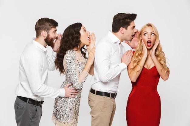 Grupa czterech pozytywnych ludzi elegancko ubranych, opowiadających sobie tajemnice izolowanych na białym