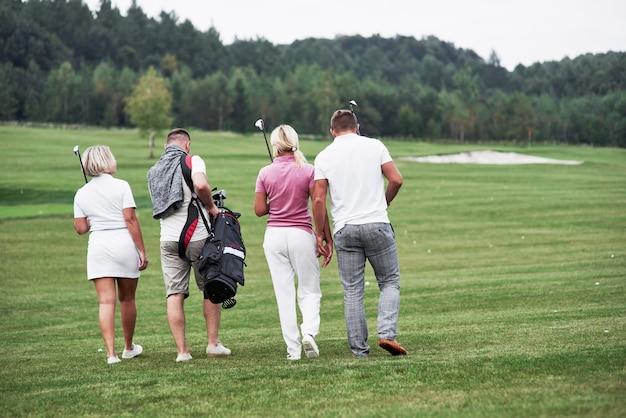 Grupa czterech przyjaciół niosących sprzęt golfowy jadąca do następnego punktu pola.