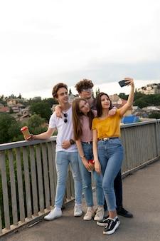 Grupa Czterech Przyjaciół Spędzających Razem Czas Na świeżym Powietrzu I Robiących Selfie Darmowe Zdjęcia