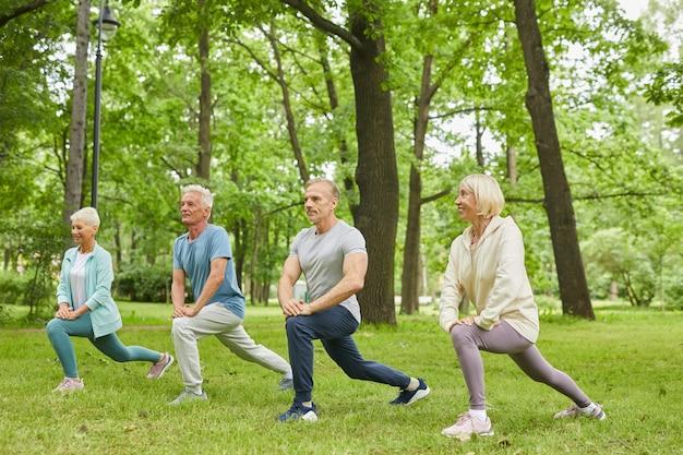 Grupa czterech starszych mężczyzn i kobiet noszących ubrania sportowe robi ćwiczenia rozciągające nogi w parku