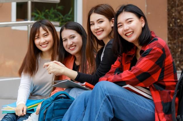 Grupa czterech studentek trzymających książki, siedzących i dzielących czas