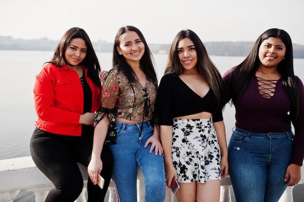 Grupa czterech szczęśliwych i ładnych latynoskich dziewcząt z ekwadoru pozowała nad jeziorem.