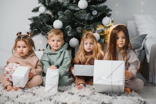 Grupa czwórki dzieci z prezentami na wigilijnym przyjęciu