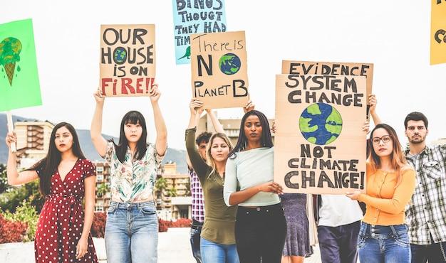 Grupa demonstrantów na drodze, młodzi ludzie z różnych kultur i ras walczą o zmianę klimatu. globalne ocieplenie i koncepcja środowiska