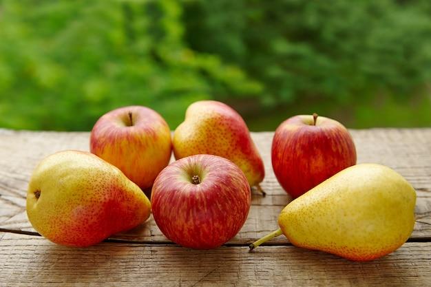 Grupa dojrzałych gruszek i jabłek na zielonym tle liści