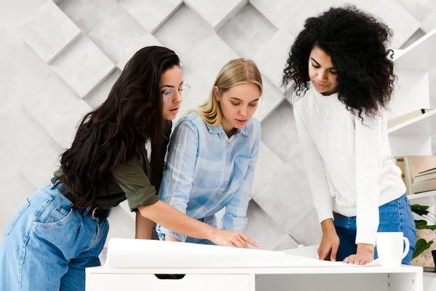 Grupa dorosłych kobiet pracujących razem nad projektem