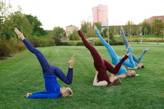 Grupa dorosłych kobiet uczęszczających na jogę na zewnątrz w parku