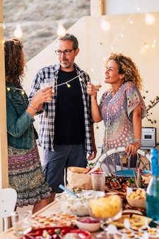Grupa dorosłych przyjaciół cieszyć się wieczorem z koktajlami i jedzeniem na rustykalnym drewnianym stole - przyjaźń i wspólna zabawa w imprezowym stylu życia - koncepcja celebracji w domu